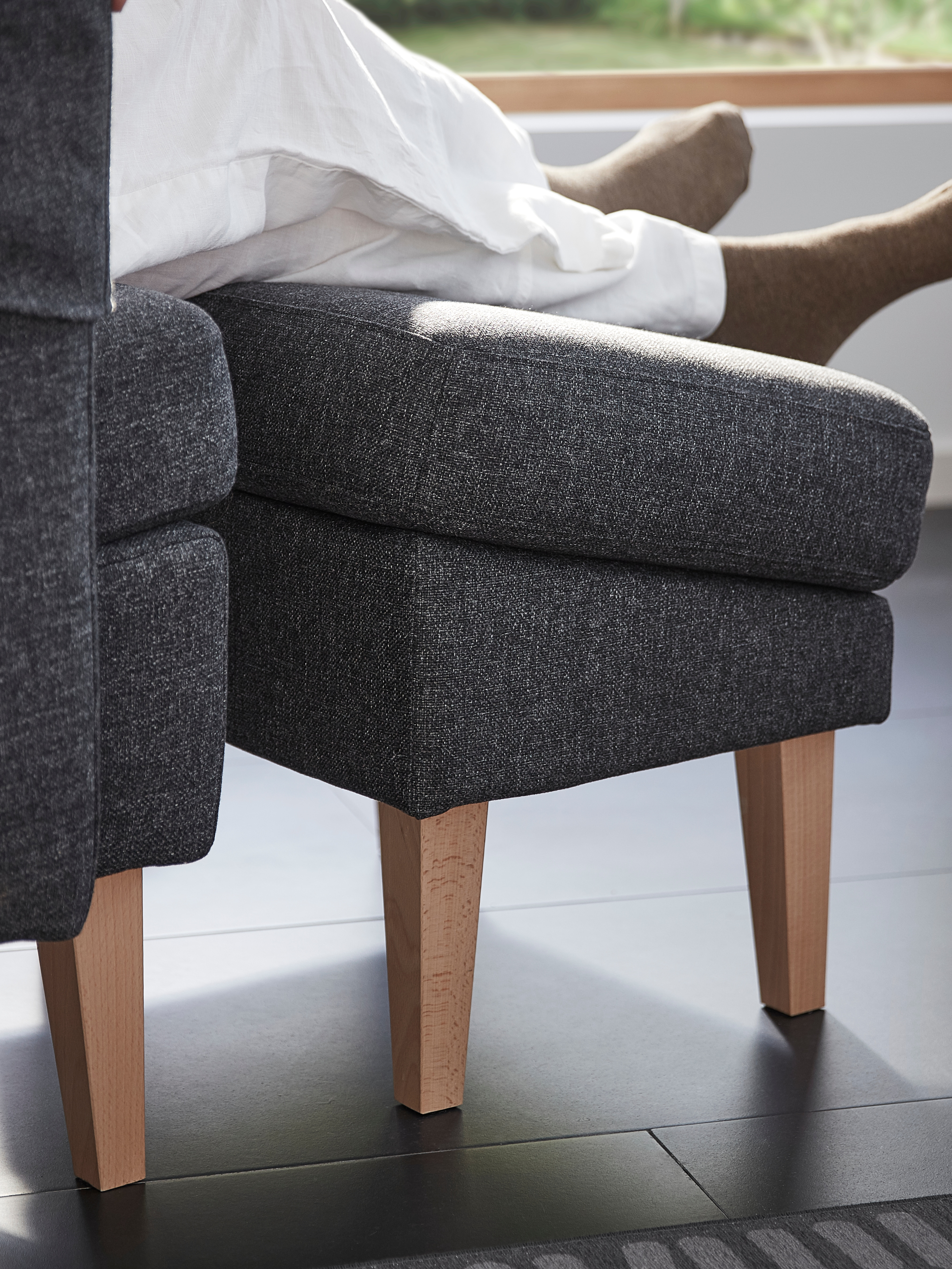 A side view of a person's legs and feet on a slanted Gunnared dark grey OMTÄNKSAM footstool beside a matching armchair.