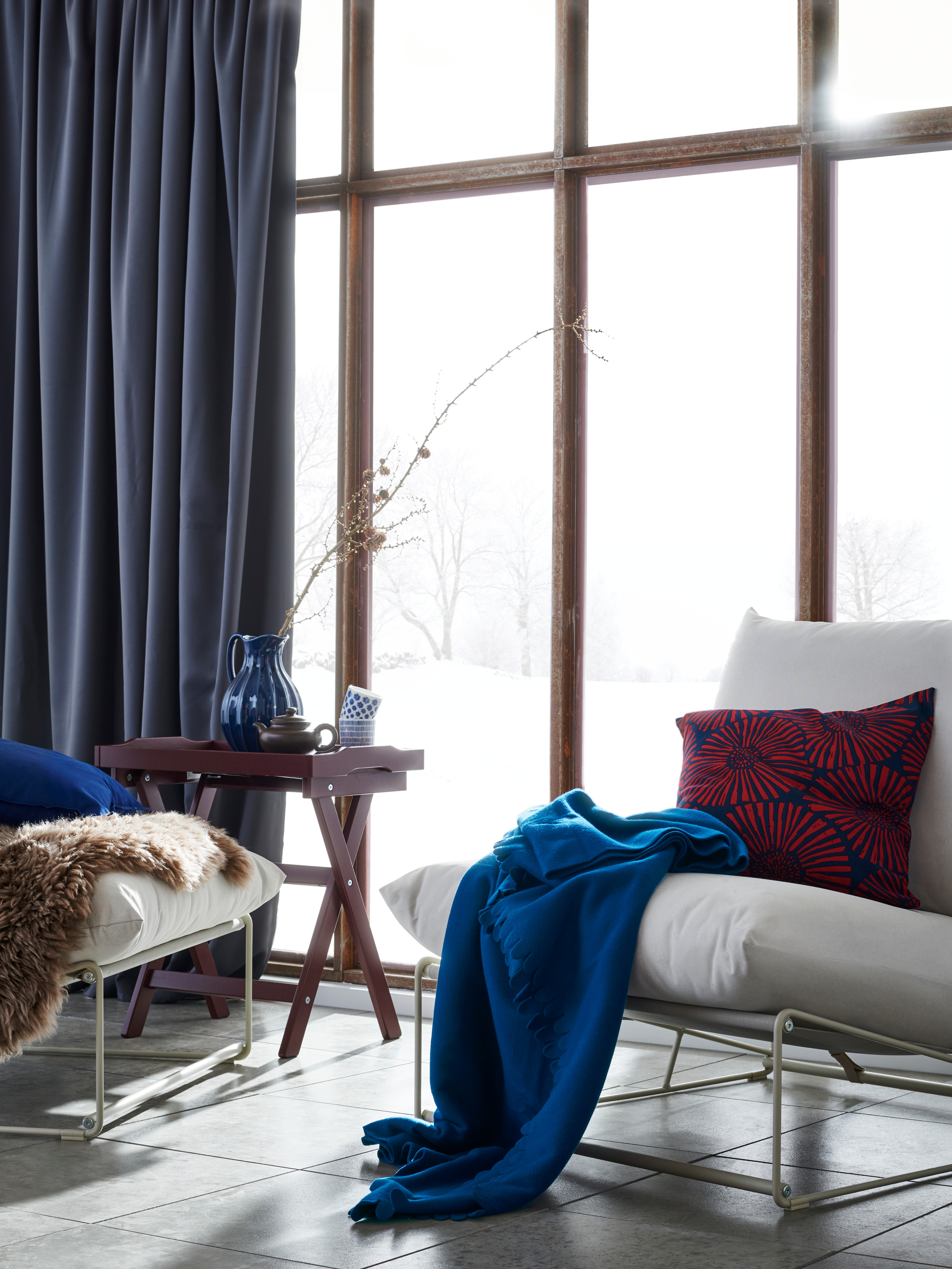 Dvije unutarnje-vanjske lounge stolice u popločanoj sobi sa staklenom stijenom i snijegom vani, s plavom POLARVIDE laganom dekom i ukrasnim jastucima.