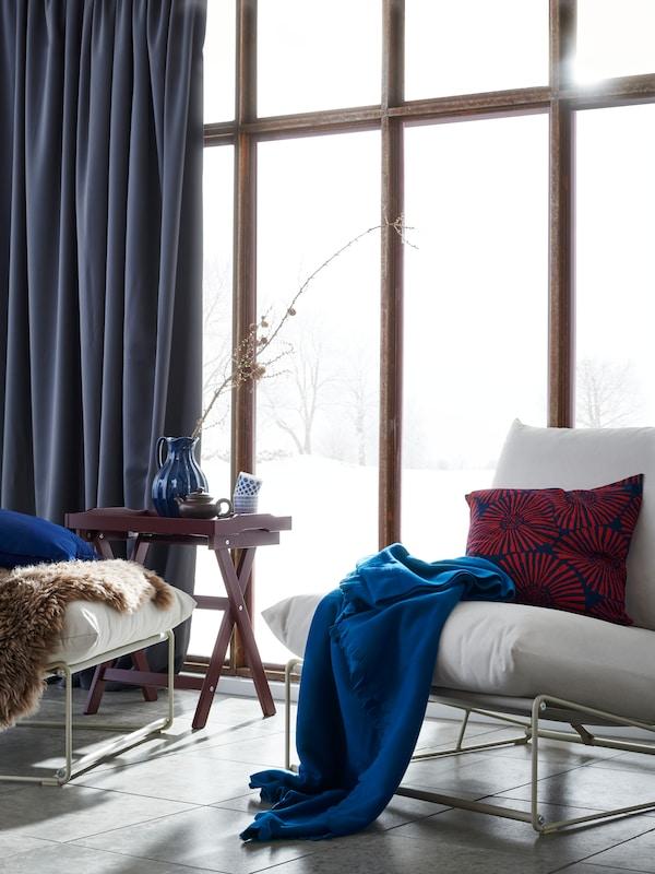 Deux fauteuils int/ext avec un plaid POLARVIDE bleu et des coussins dans une pièce carrelée, mur vitré, neige à l'extérieur.