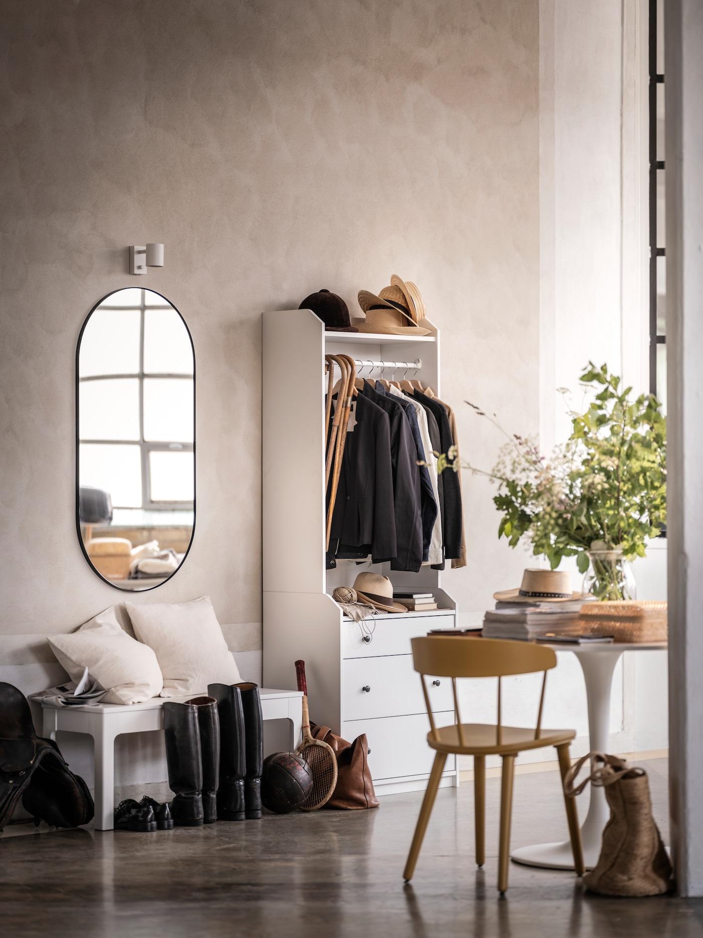 В прихожей со стенами, облицованными под камень, в открытом гардеробе ХАУГА висят пиджаки. На стене — овальное зеркало.