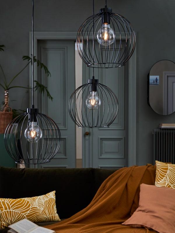 Trois suspensions GRINDFALLET équipées d'ampoules LED décoratives pendent du plafond dans un salon, un après-midi d'automne.
