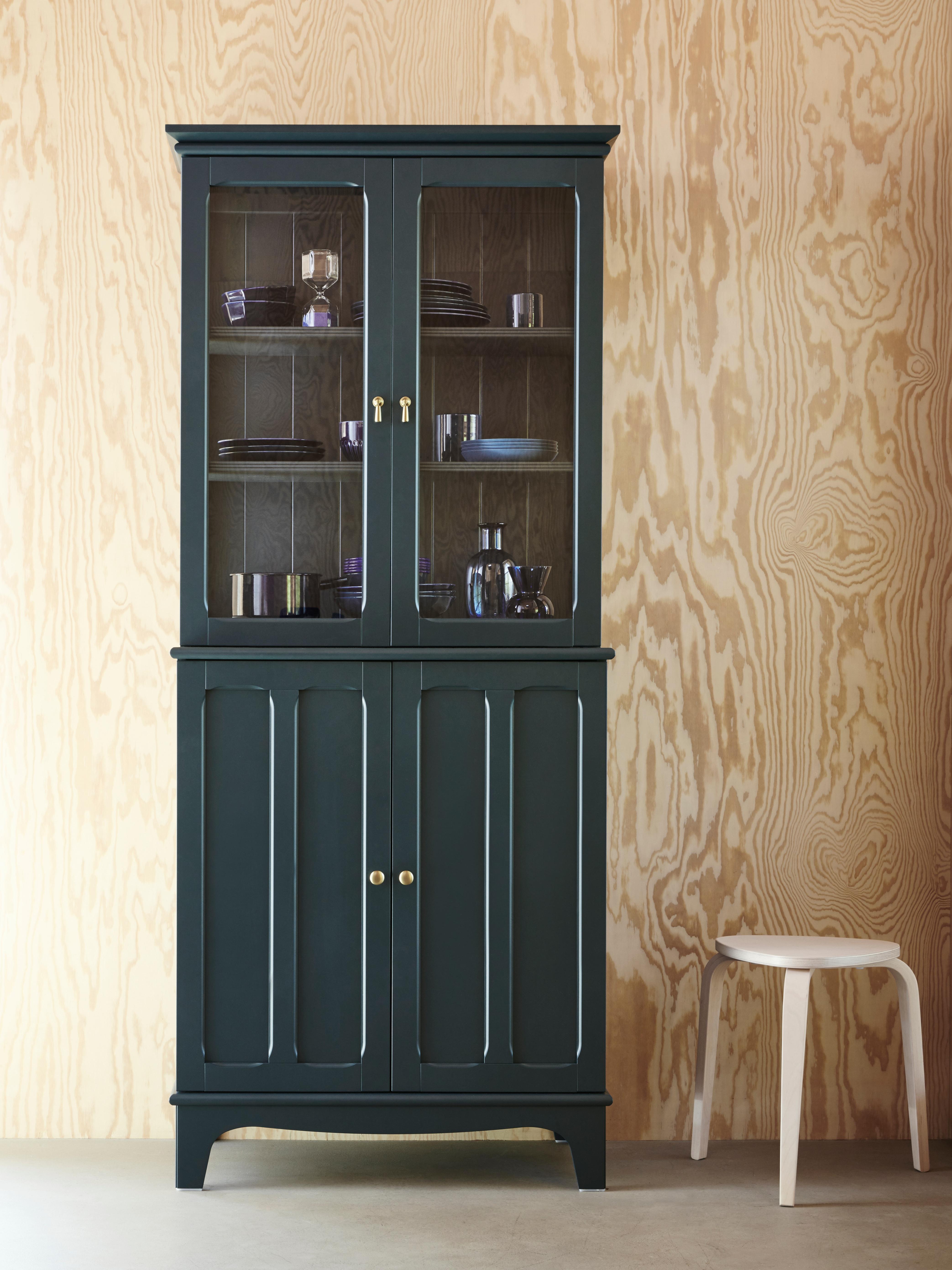 Ein mit Geschirr gefüllter LOMMARP Schrank mit Vitrinentüren in dunklem Blaugrün vor einer Sperrholzwand.