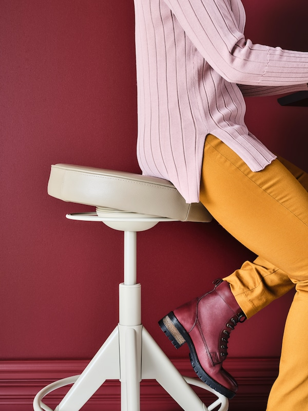A women wearing blue jeans and holding a pink cup sitting on a LIDKULLEN sit/stand support.