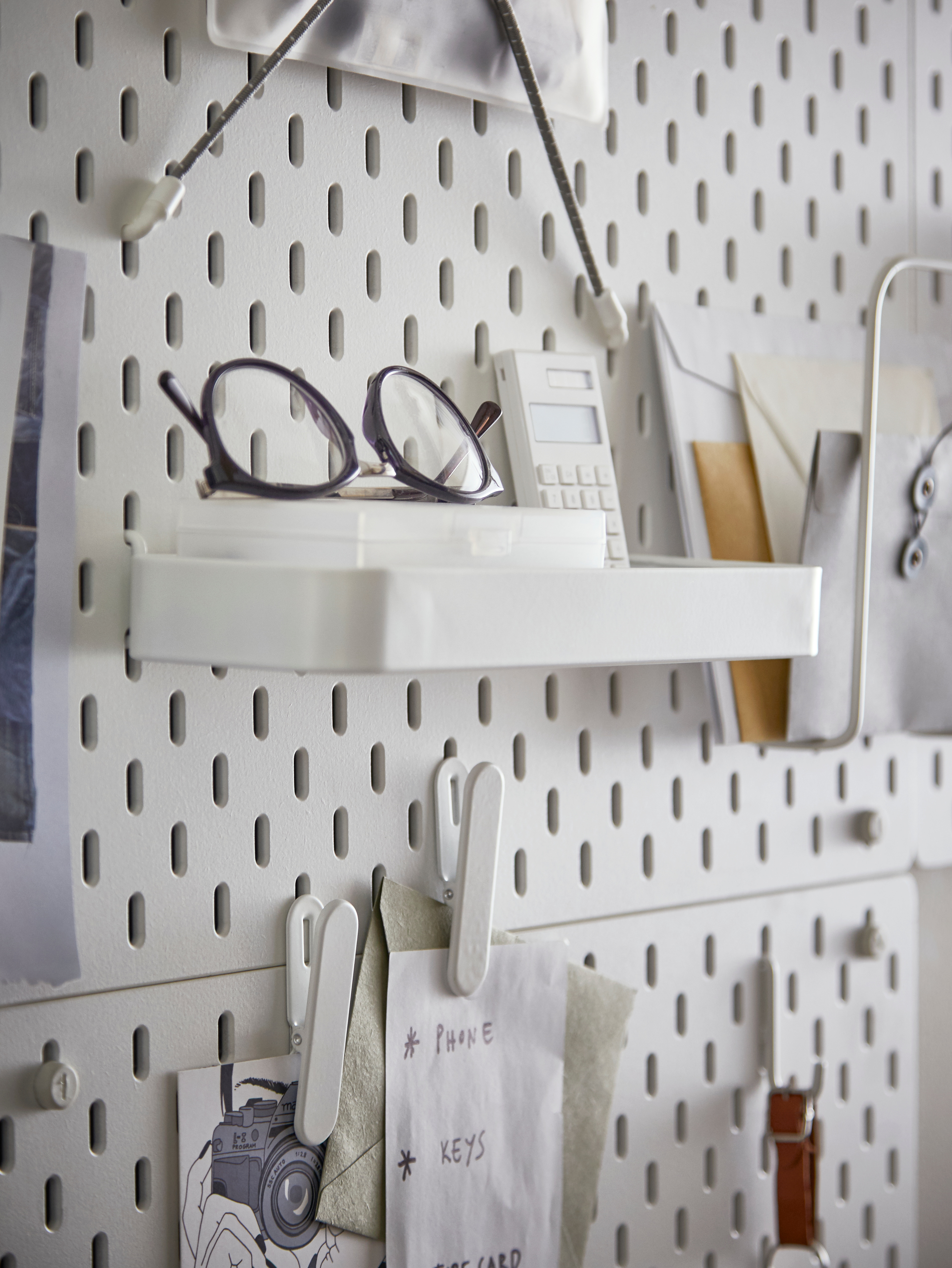 Workspace with white pegboard, white paper clips with notes, white shelf with reading glasses and calculator, envelopes.