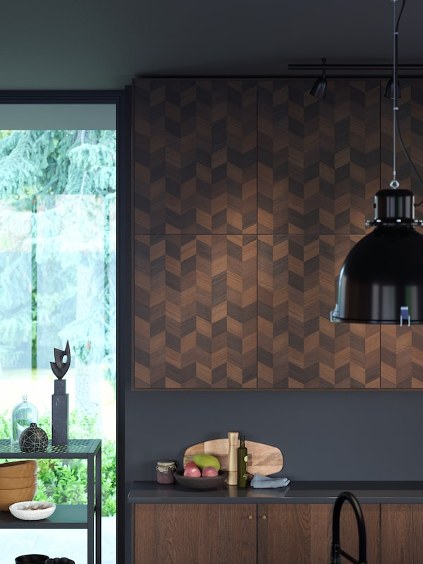 Wooden cabinets on a wall with a chevron pattern on the doors, black pendant lamp, a bowl of fruit on the black worktop.
