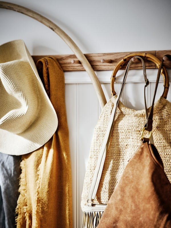 Une patère à 6 boutons HÖVOLM en chêne sur un mur blanc avec soubassement en lambris de bois. Des sacs, chapeaux et foulards y sont accrochés.