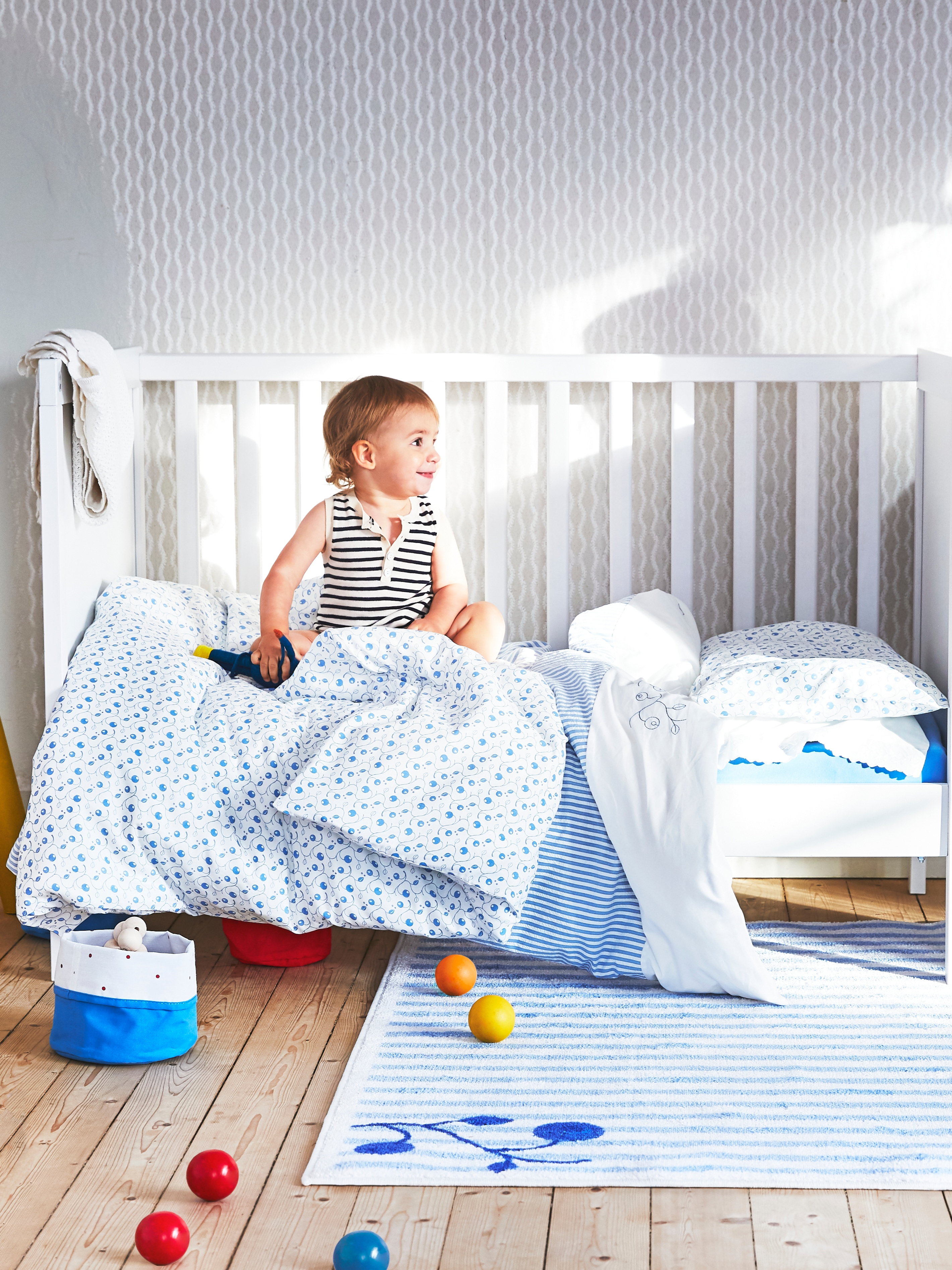 Toddler sits upright on a white SUNDVIK crib, that has one of its sides removed, with lots of blueberry-motif bedding on top.
