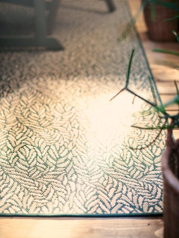 Un tapis d'extérieur SKELUND à motifs vert ajoute une touche personnelle et permet de délimiter la salle à manger d'extérieur sur une terrasse en bois.