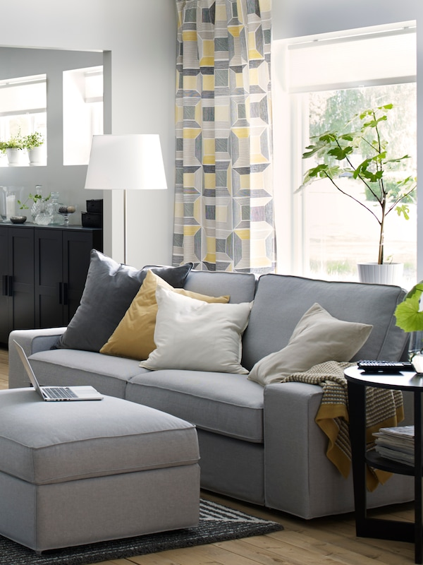 A KIVIK sofa in light gray with several throw pillows, a standing lamp behind it and a tray table in black beside it, on a black and white striped rug.