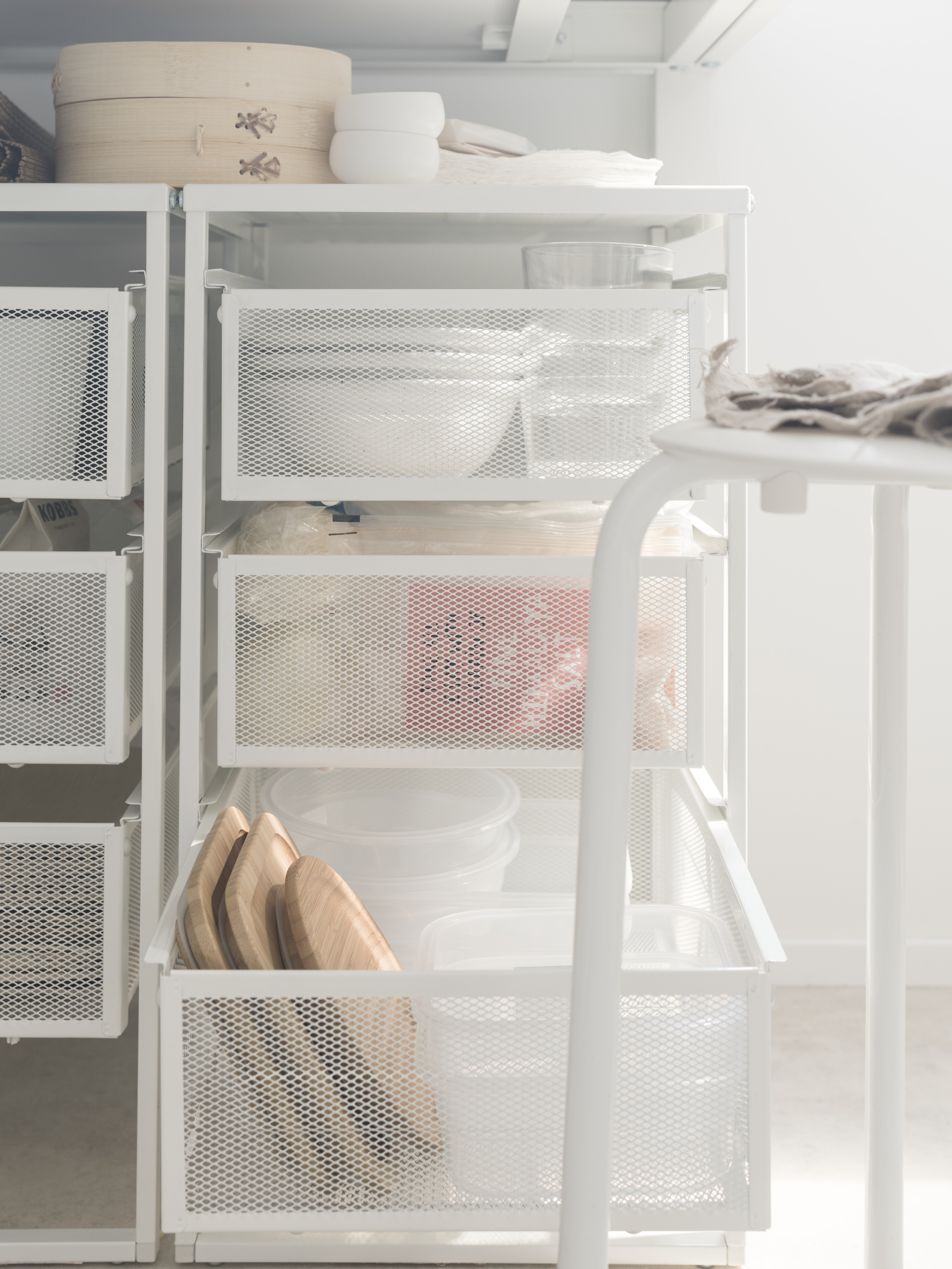 Two white metal mesh LENNART drawer units hold tableware and food storage boxes under a kitchen table, by a white stool.