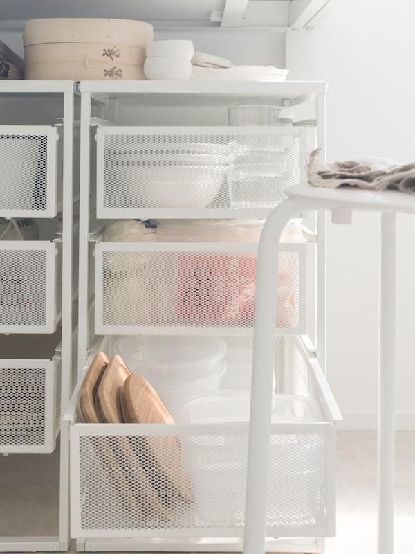 Zásuvky z bílé síťoviny s krabicemi na nádobí a potraviny.