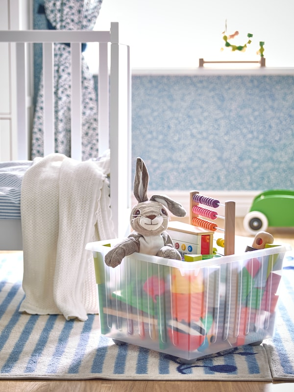 Blue coloured nursery room. White crib with white blanket falling off edge. Blue and white striped rug with clear storage bin. Bin is holding toys and small stuffed rabbit