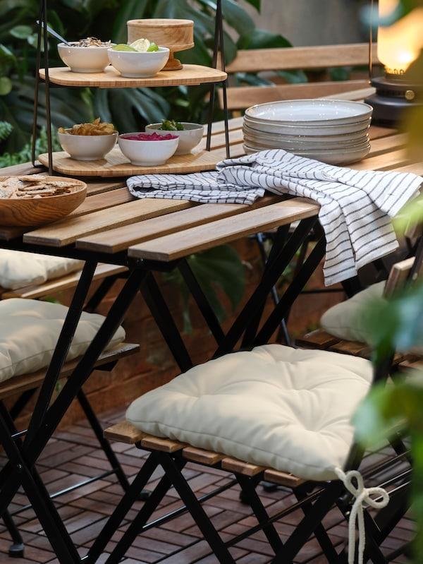 tarno tuintafel en twee stoelen, bedekt met stoelkussens en een gedekte tafel