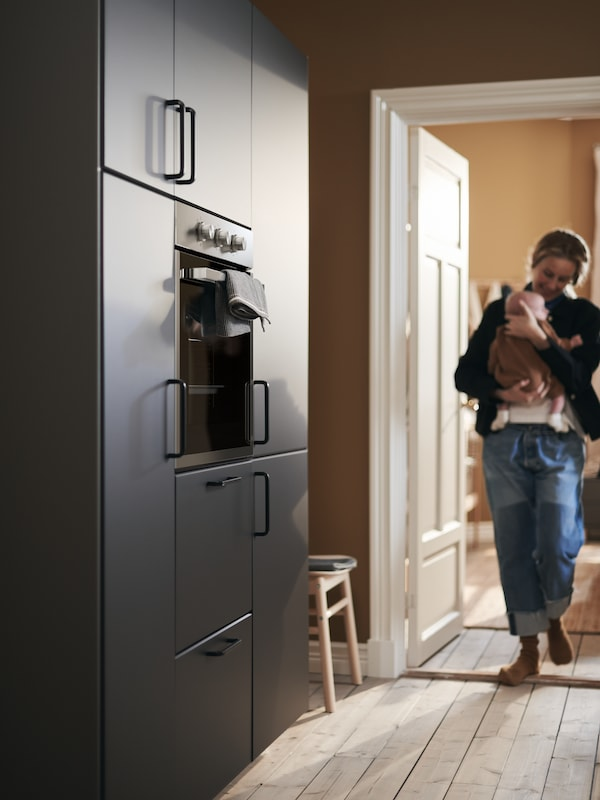 A mother cradles her baby as she enters the kitchen, approaching a wall of cabinets with KUNGSBACKA fronts.