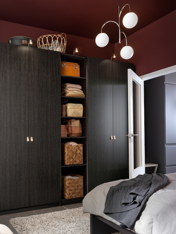A PAX wardrobe with FORSAND black-brown doors and shelves holding baskets and other items stands in a bedroom.