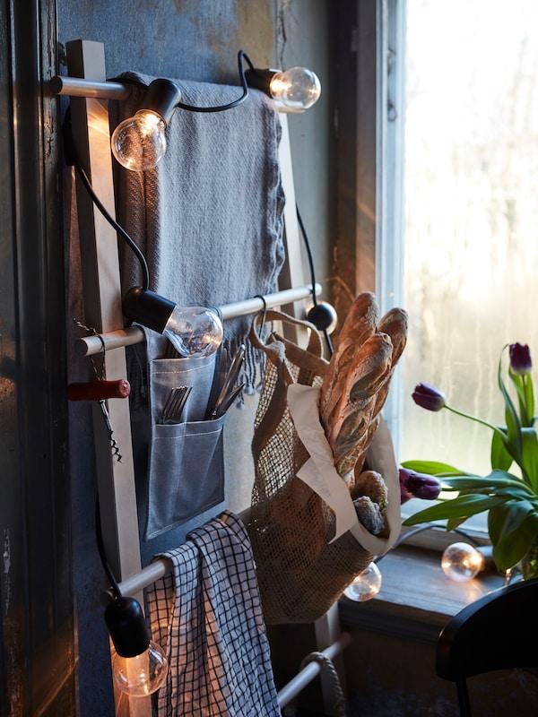 U rustikalnoj prostoriji rasvjetnim je lancem ukrašen stalak za ručnike koji služi kao pametno rješenje za odlaganje i uštedu prostora.