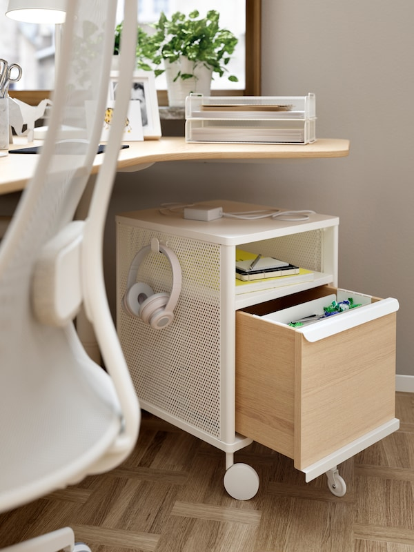 Storage beneath a work desk, the drawers open, a workplace chair and various items on the desk including a potted plant.