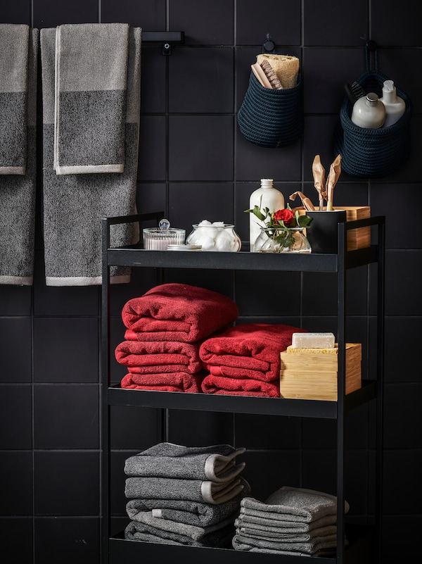 A black NISSAFORS trolley holding HIMLEÅN towels in red and grey, toiletries, and DRAGAN boxes, against a black tiled wall.