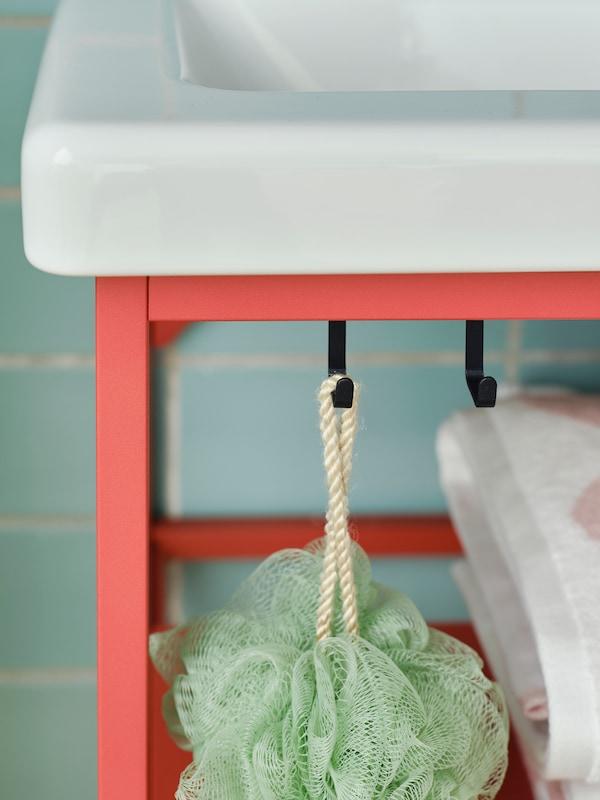 Zbliżenie na czarne haczyki na czerwonopomarańczowej szafce pod umywalkę ENHET ustawioną w łazience. Na jednym z haczyków wisi gąbka kąpielowa.