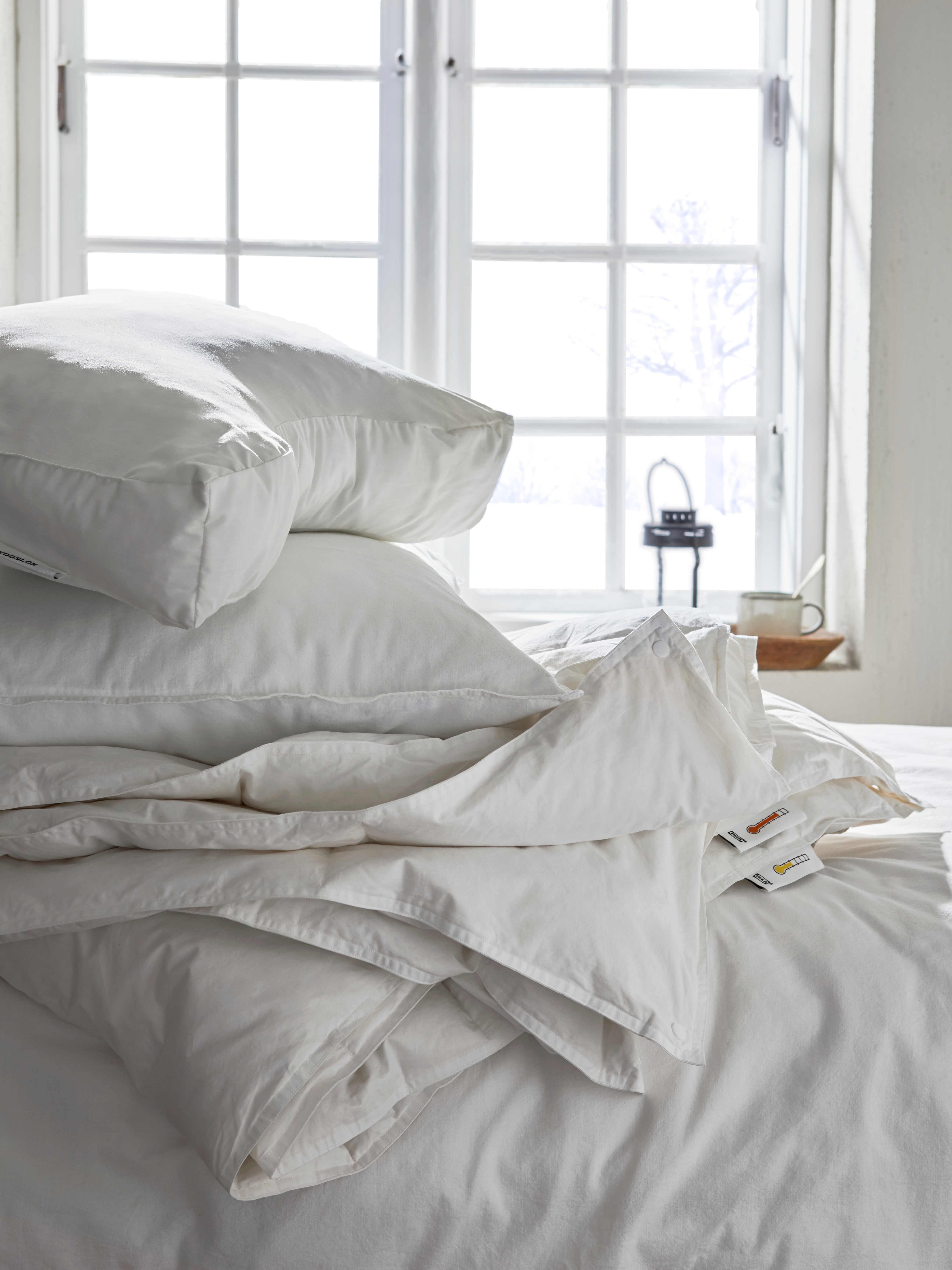 FJÄLLARNIKA double duvet and pillows on a white bed with a white wall and window in the background.