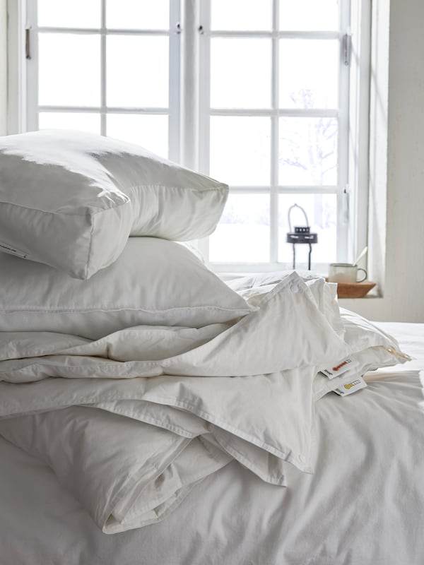 Folded bedding in a pile on an unmade bed, by a window with a teacup and a lantern on the windowsill.