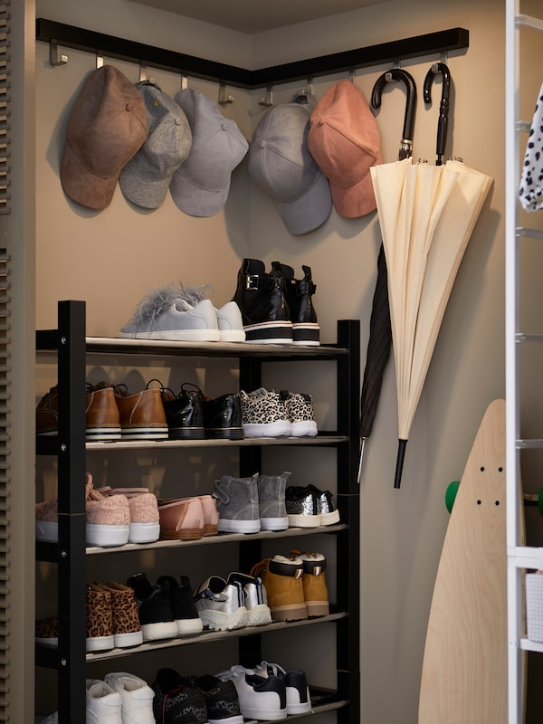 Peaked caps and umbrellas hang from the hooks on two, black, TJUSIG hangers on a corner wall above a black, TJUSIG shoe rack.