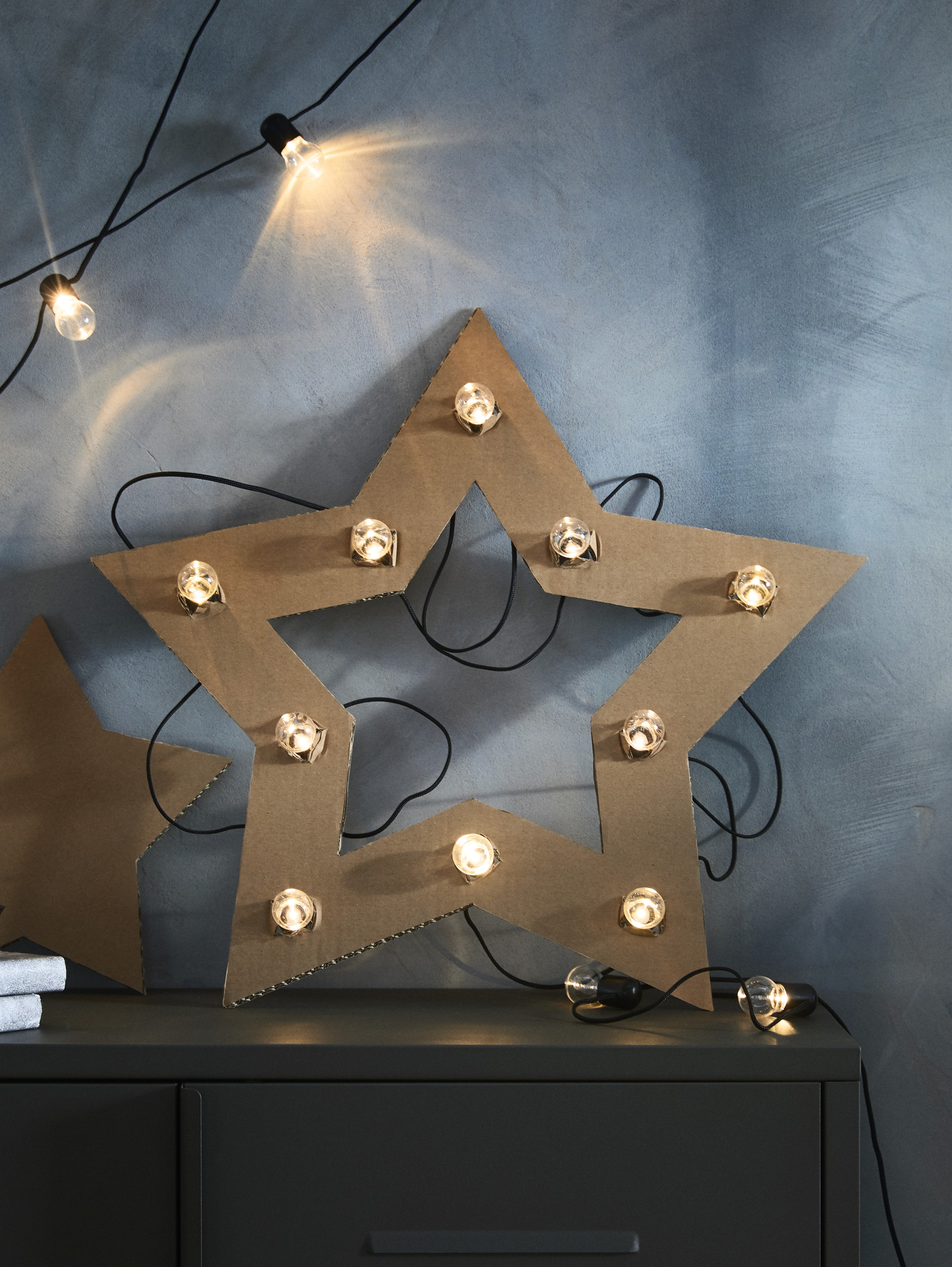 The bulbs of a BLÖTSNÖ LED lighting chain poke through holes in a cardboard cut-out of a star that sits on a metal cabinet.