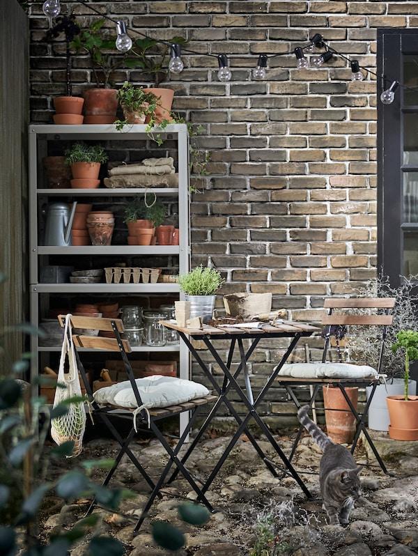 En reol af metal med urtepotteskjulere og krukker på hylderne står ved en murstensmur bagved et caféslt med et bord og to klapstole.