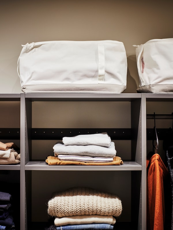 A LACKISAR storage case sits on top of an open AURDAL wardrobe, with folded clothes lying on the shelves below.