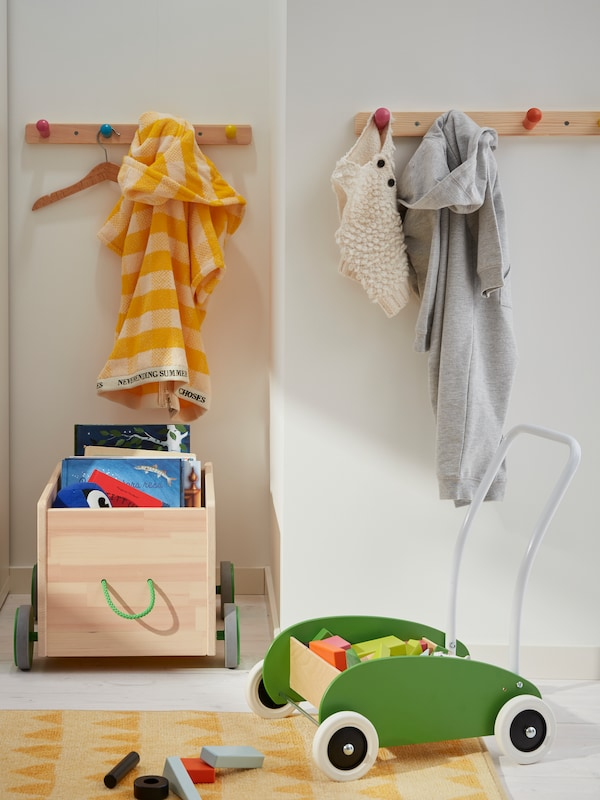 A MULA toddle truck and a FLISAT toy storage with wheels stand on the floor. Clothes hang from FLISAT knob racks on the wall.