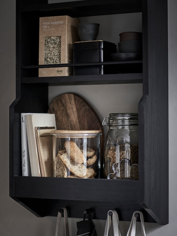 A black shelf unit on a grey wall, with jars of biscuits, books, boxed food, and hooks below with hanging tote bags.