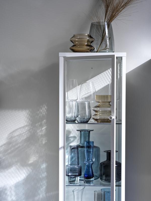 Plusieurs types de vases et verres en cristal exposés et rangés dans une vitrine BAGGEBO ouverte.
