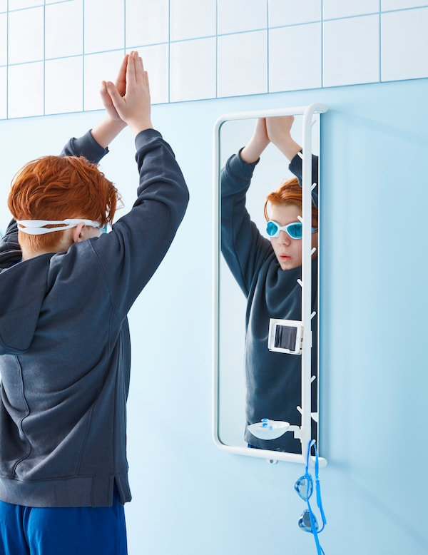 A child with red hair is wearing swimming goggles and holding their arms up in a diving pose in front of a MÖJLIGHET mirror.