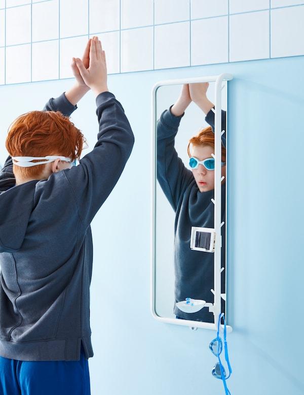 Barn med rött hår och simglasögon håller upp armarna i en dykpose framför en MÖJLIGHET spegel.