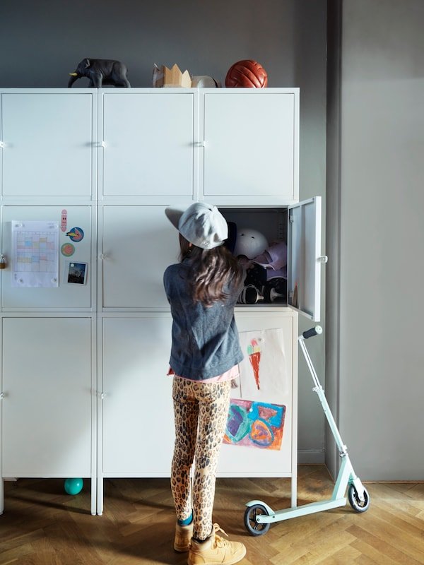 A young girl wearing a cap with a scooter, by a white storage unit with one of the doors open, various items inside.