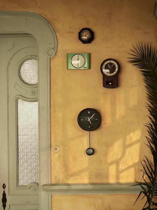 Ceasul de perete STURSK negru cu detalii aurii și un pendul care atârnă de acesta. Este amplasat pe un perete cu ceasuri vechi de perete.