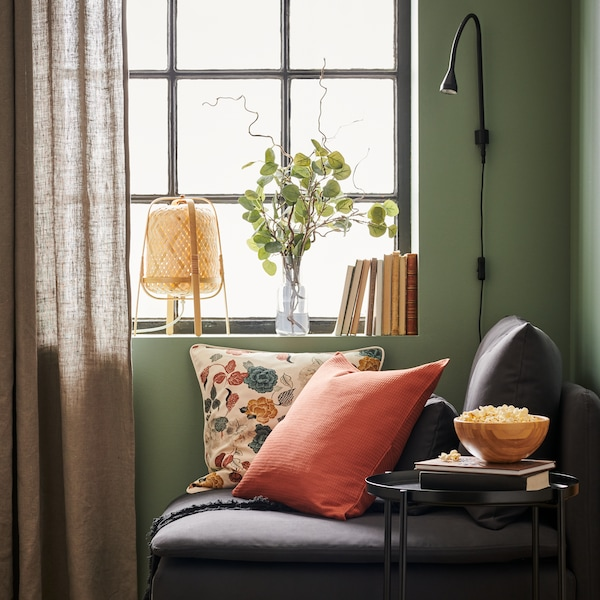 A small grey sofa, heaped with colourful cushions, next to a window.