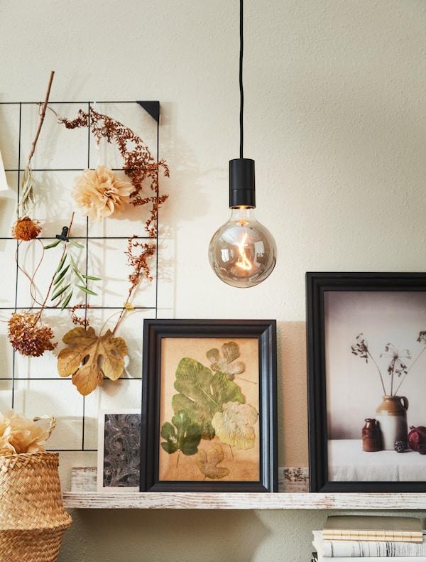 En höstig känsla där torkade blommor pryder en anslagstavla och inramade posters i höstiga toner står lutade mot väggen.