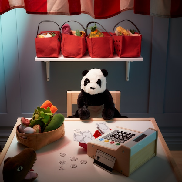 A stuffed toy panda seated at a table with a toy cash register and plush vegetables.