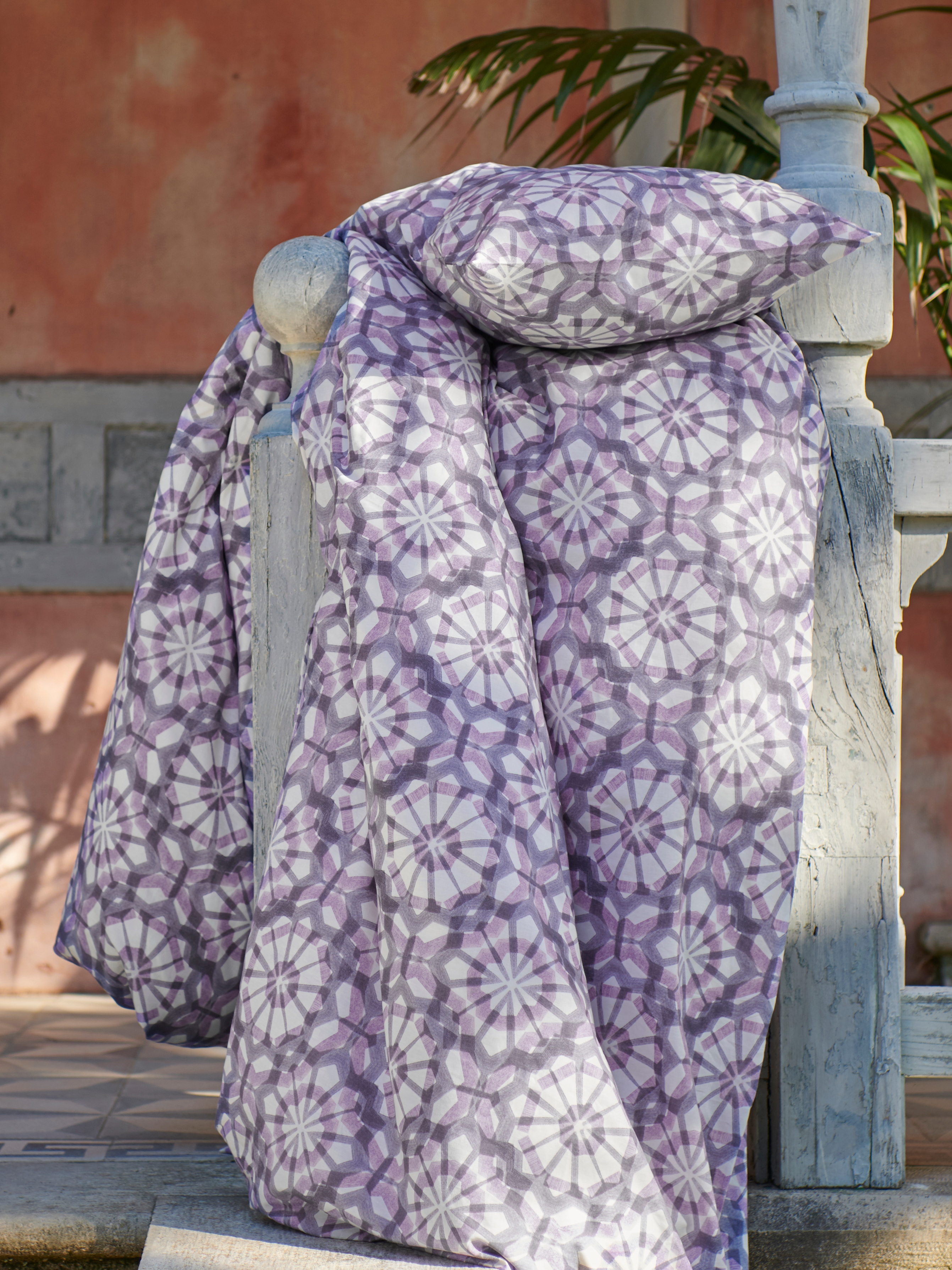 VATTENFRÄNE quilt cover and pillowcase set with a starry-flowered, geometric pattern in purple and white is on a porch rail.