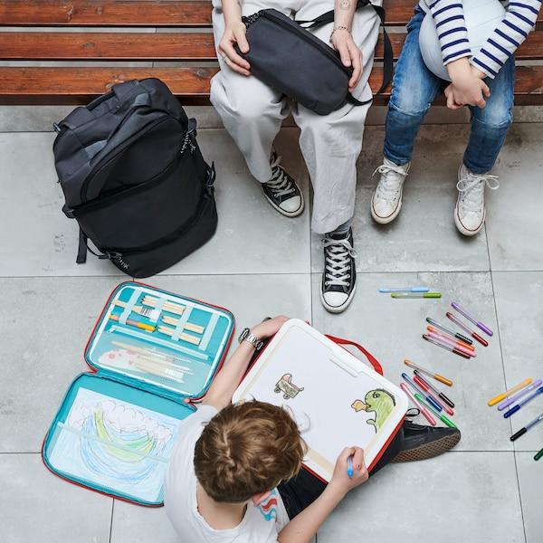 Ребенок сидит за детским столом ФЛИСАТ и вырезает что-то из бумаги. На столе лежат краски МОЛА и разная бумага.