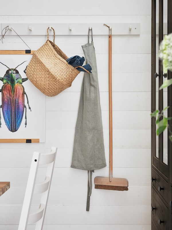 A KUBBIS hook rack on a wall, hanging from it are a BILD beetle poster, a FLADIS basket, a wooden broom and a grey apron.