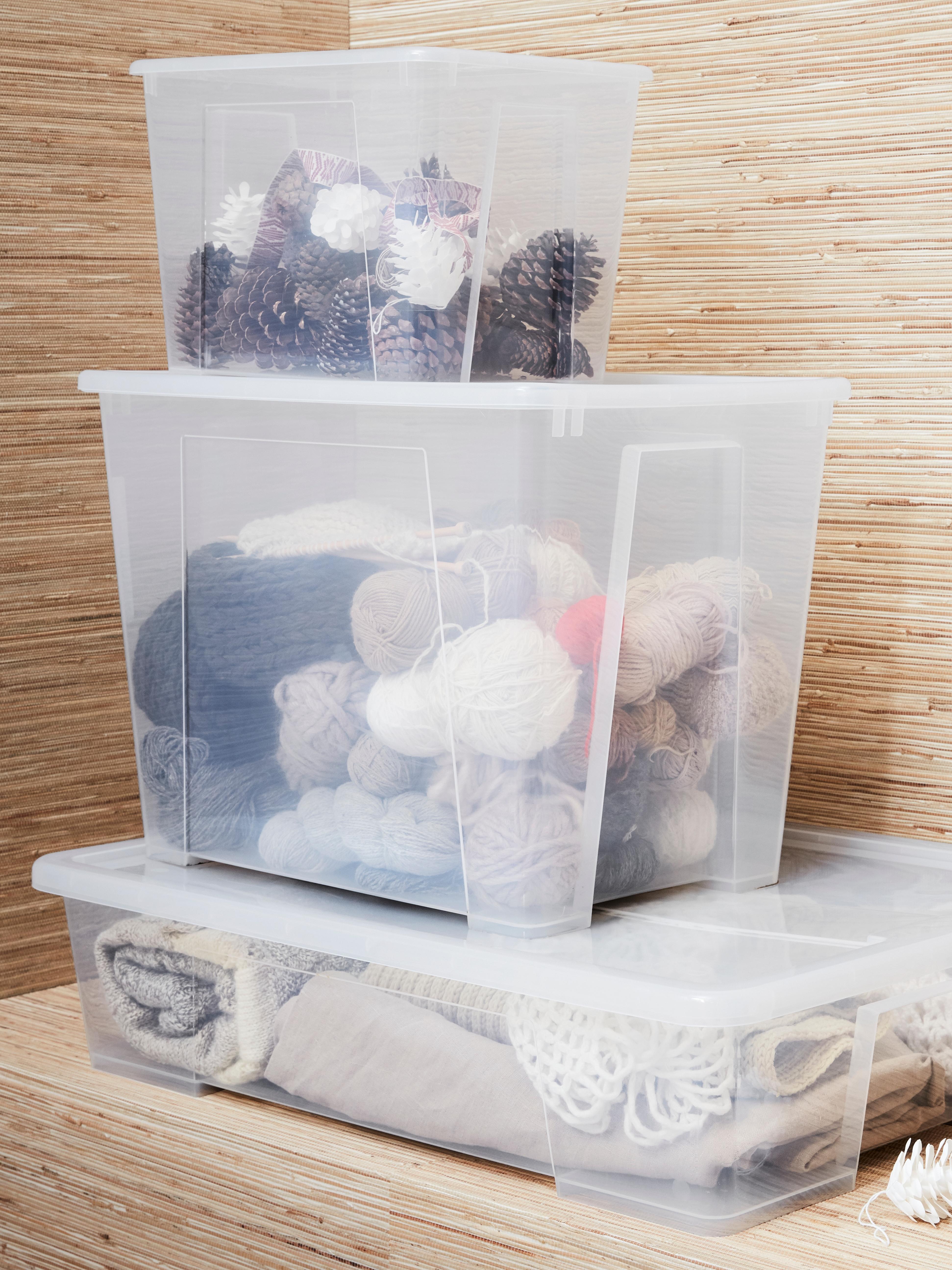Egurrezko armairua tamaina desberdinetako hiru plastikozko kaxa gardenekin, bata arroparekin eta bestea bolekin.