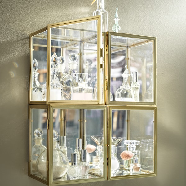 Four wall-mounted, gold-colour BOMARKEN display boxes grouped tightly together and filled with decorative glassware.