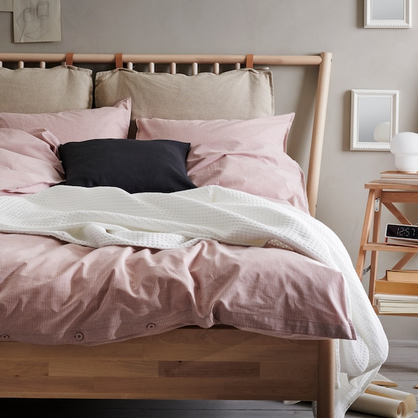 A bed with casually layered pink and white textiles.