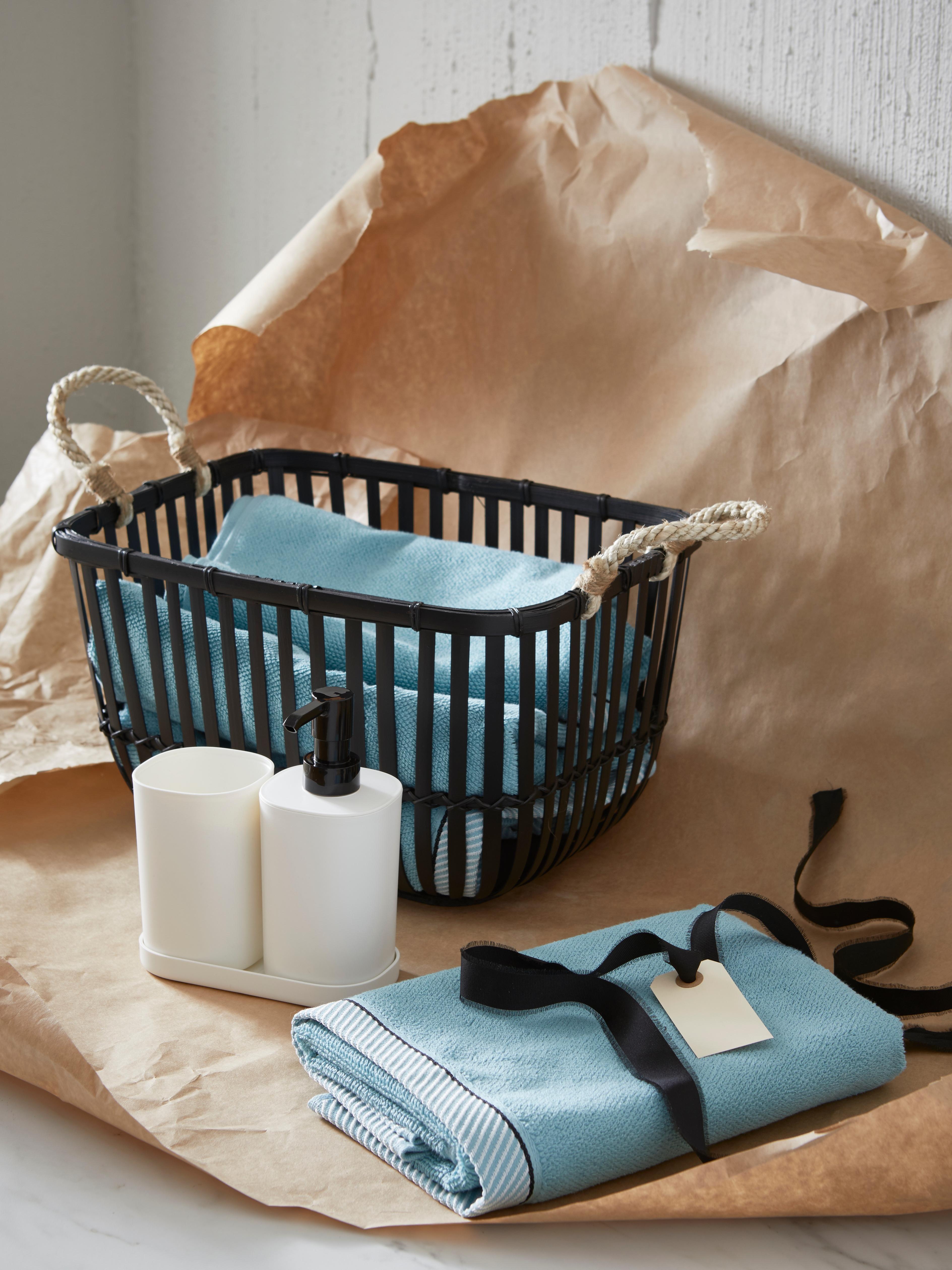 STORAVAN kupaonski set s dozatorom, plavim ručnicima u košari na smeđem papiru za omatanje s crnom vrpcom.