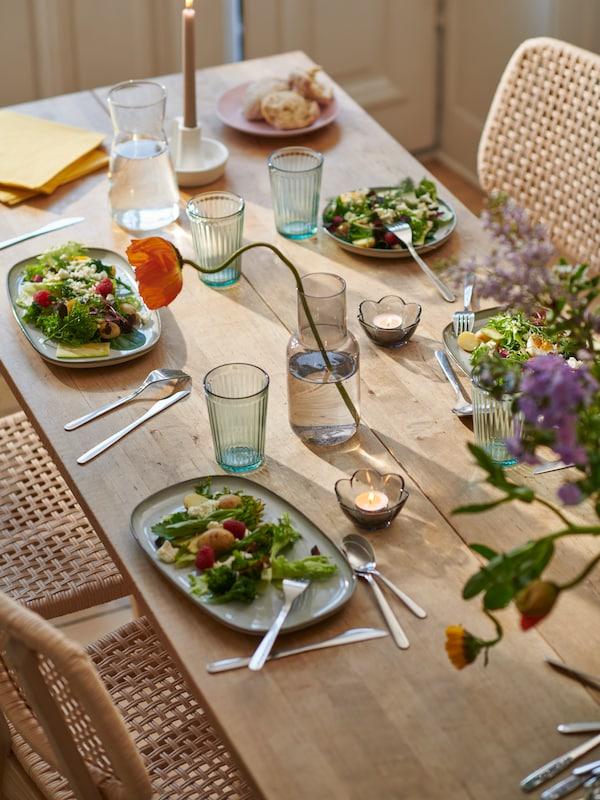 Una comida ligera servida en los platos GLADELIG con cubiertos FÖRNUFT sobre una mesa de madera decorada con velitas y flores.