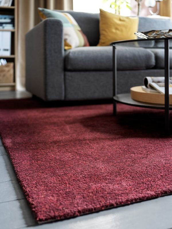A wine-red rug with a coffee table on it holding various items, a grey sofa in the background with cushions.