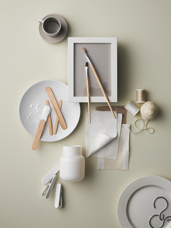 A fehér árnyalaiban tündöklő különböző elemeket látunk szétszórtan: közöttük egy fehér FLITIGHET kistányért, egy bézs DINERA kávéscsészét alátéttel, zsinórokat és textildarabokat.