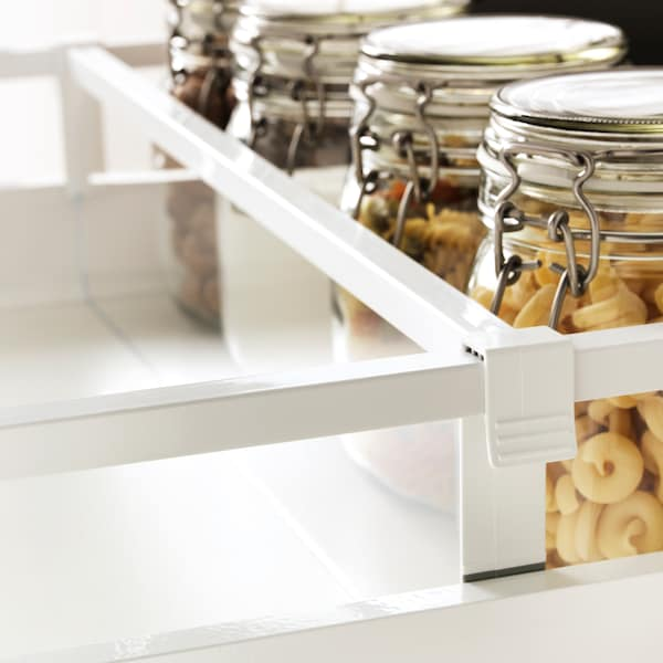 A pulled-out kitchen drawer with MAXIMERA divider and four KORKEN jars with lid containing pasta and other dried foods.